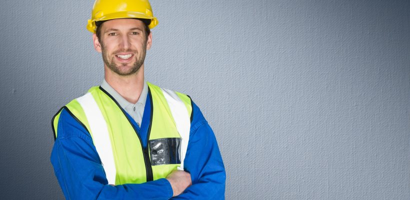 Portrait of construction worker standing with his arms crossed against grey background